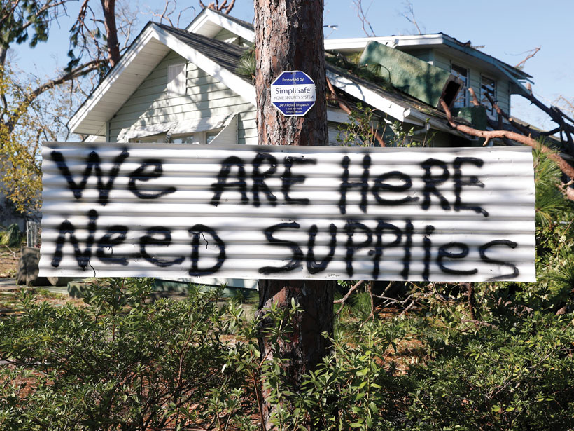 A sign hangs on a tree in front of a house damaged by Hurricane Michael in Panama City, Fla., in 2018.