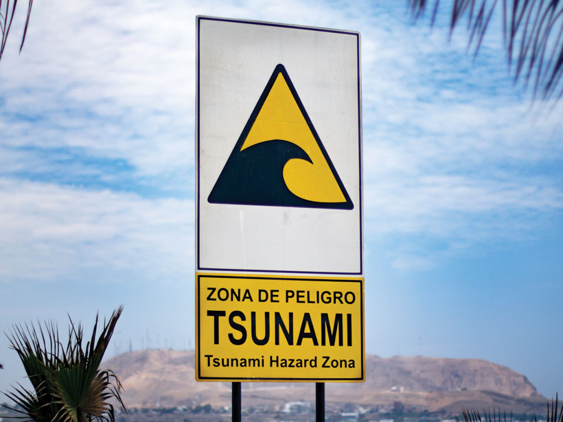 A sign in Spanish near the ocean in Lima, Peru, warns of danger in a tsunami hazard zone.