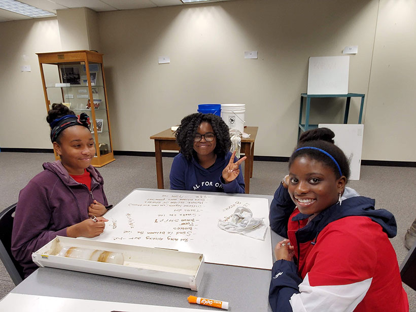 Middle school students sitting around a table at Ohio State University with a homemade ice core