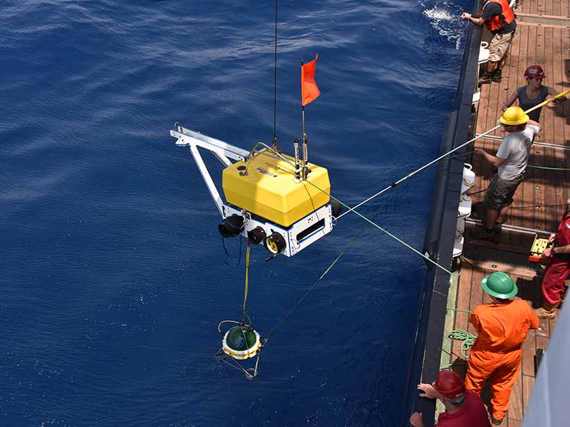 An ocean bottom seismometer being lowered into the ocean by a research crew