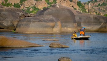 Fishermen work from a small boat on a river in southern India with large boulders in the background