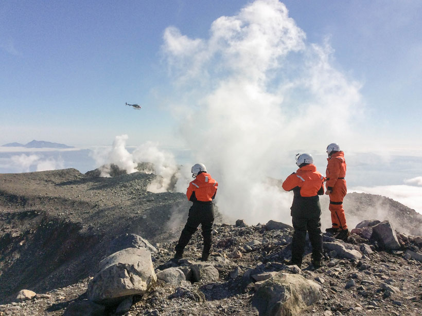 Scientists in flight suits stand atop the summit of a volcano with steam rising nearby and a helicopter in the distance