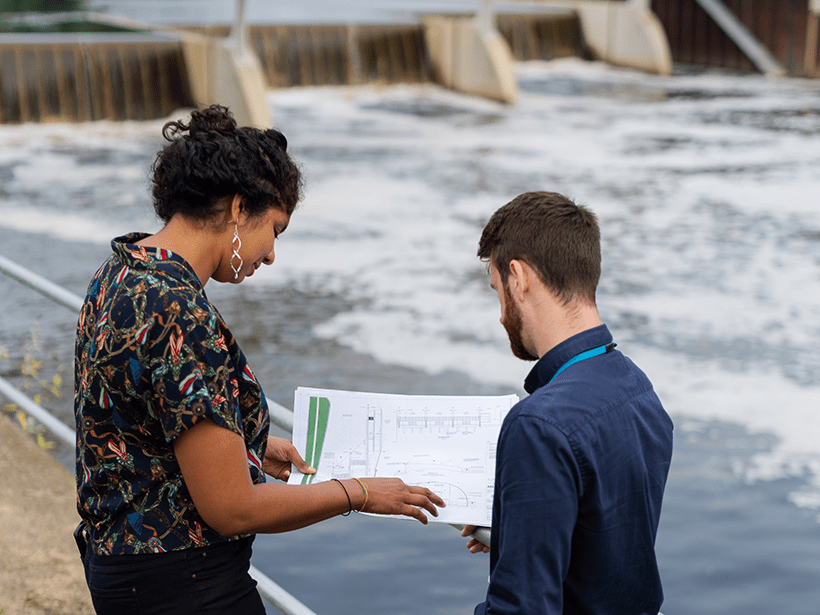 Two engineers talk in front of a bridge while holding a schematic