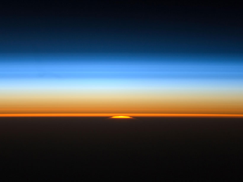 The setting Sun illuminates the layers of Earth's atmosphere in this view from the International Space Station.