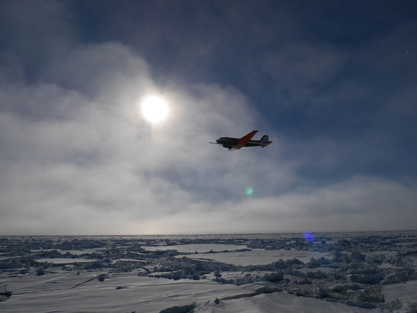 An airplane flies low over ice with the sun shining through clouds in the background