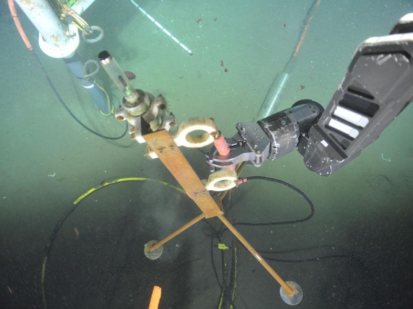 A robotic arm retrieves an underwater hydrophone