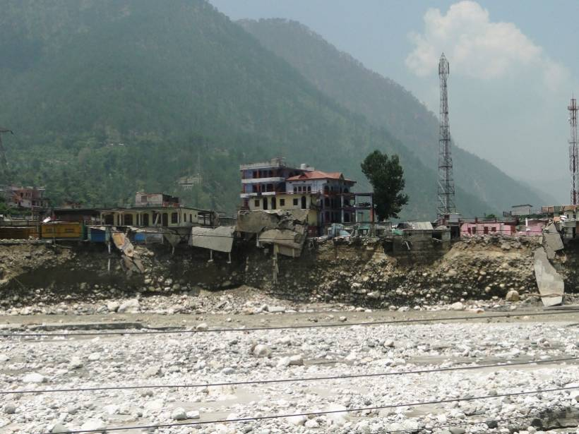 Buildings cling to a soil cliff cut away by a flood.