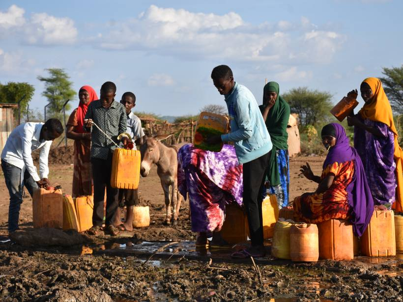 Men and women collect water at a secured borehole in Moyale, Kenya.