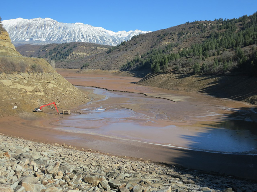 An excavator sits in the sediment-filled Paonia Reservoir in the Colorado mountains