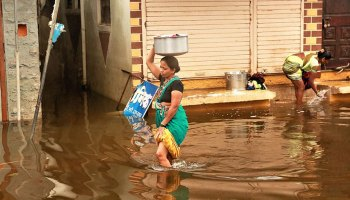 Image of a woman walking through knee-high floodwaters while balancing a large container on her head.