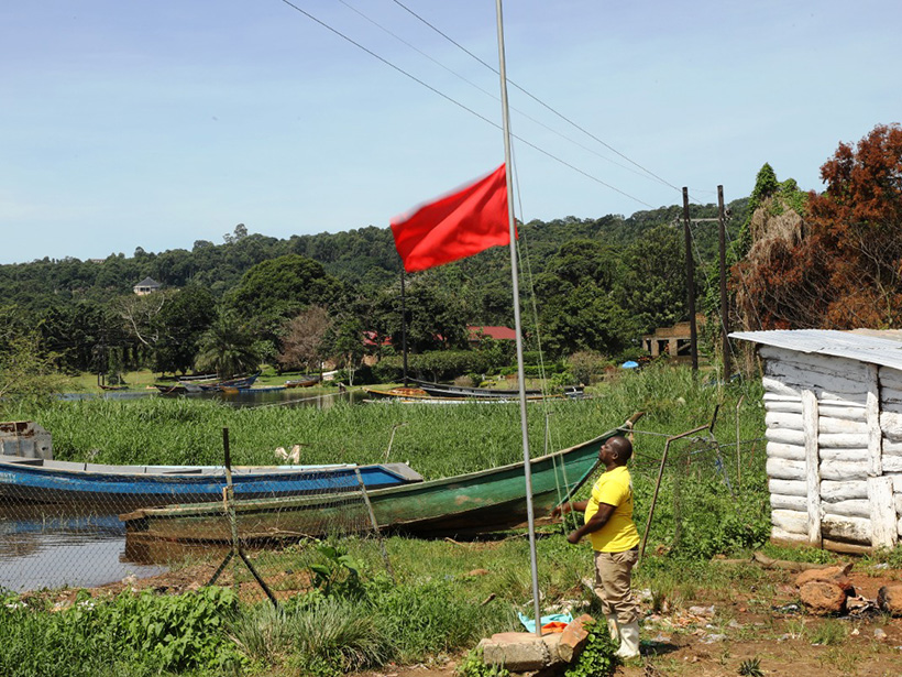 A man raises a red flag, signaling severe weather, on the shores of Lake Victoria.