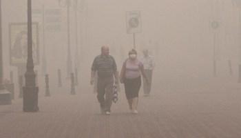 A couple walks through smog.