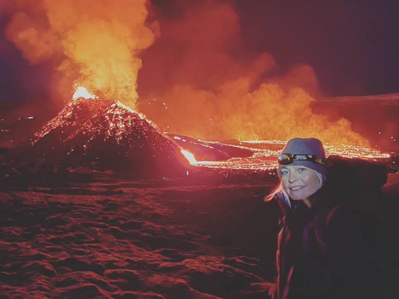 Foto de Kristin Jónsdóttir, la sismóloga de la Oficina Meteorológica de Islandia al frente, con Fagradalsfjall haciendo erupción detrás. A medida que lava naranja sale de pequeño cráter, humo anarajandizo sube al aire. El fondo de basalto negro solidificado brilla en rojo.