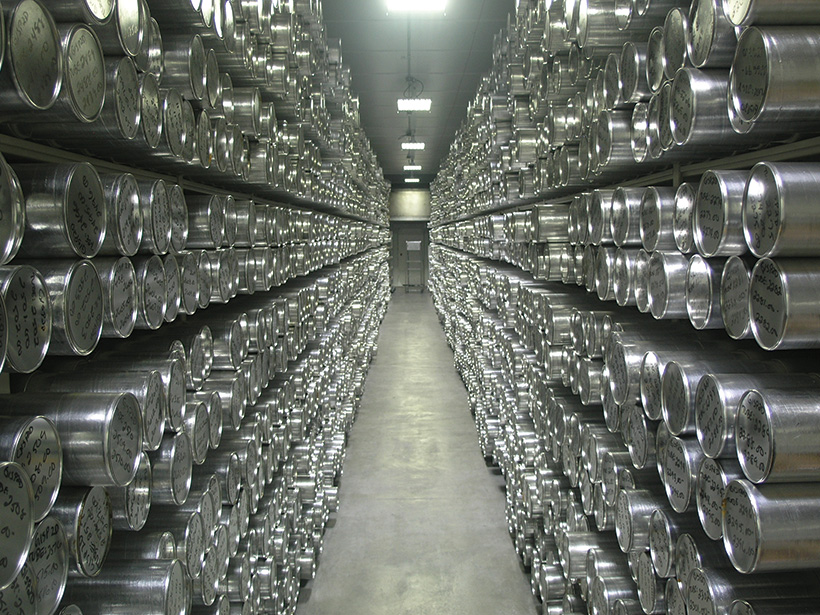 Long aisle in a storage facility lined with metal tubes of ice cores