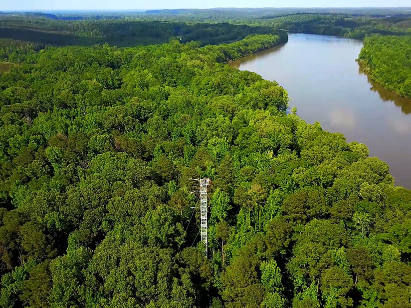Aerial view of an instrumented tower rising above forest canopy near a river
