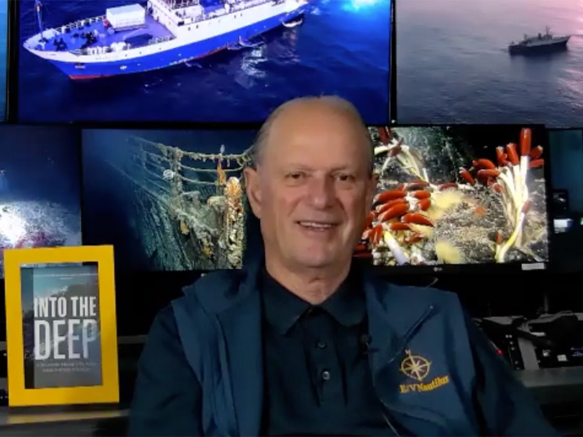 Screenshot of Robert Ballard sitting at his command center during a Zoom interview. Behind him, several computer screens show images from his explorations, including of the Nautilus, his state-of-the-art ship, the bow of the Titanic, and giant tube worms.