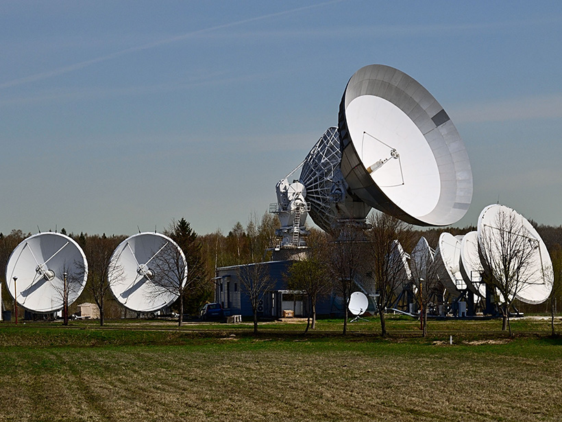 Satellite dishes deployed in a wooded field in Russia