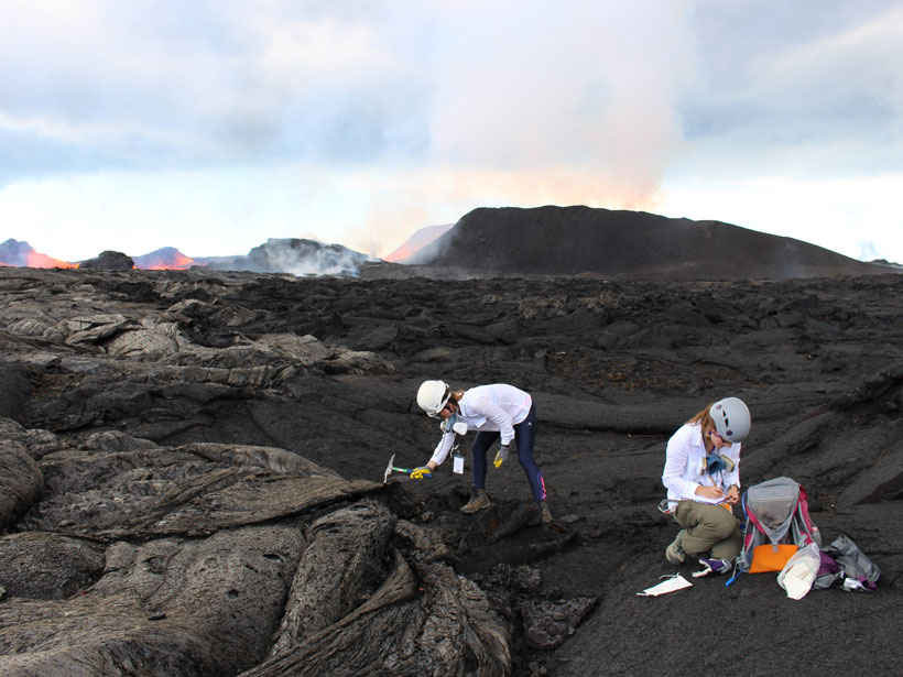 Two researchers taking samples at volcano fissure with lava in background.