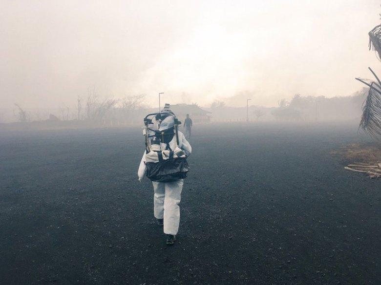 A researcher wearing a protective suit walking toward a laze plume.