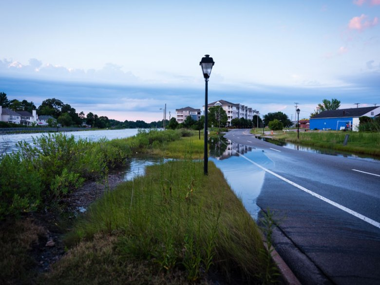 Water spills over from the Lafayette River in Norfolk, Va., onto Llewellyn Avenue just after high tide.