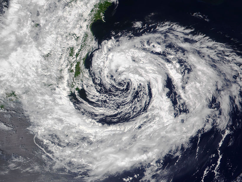White clouds swirl above blue ocean and green land as Tropical Storm Nepartak churns through the Pacific Ocean.