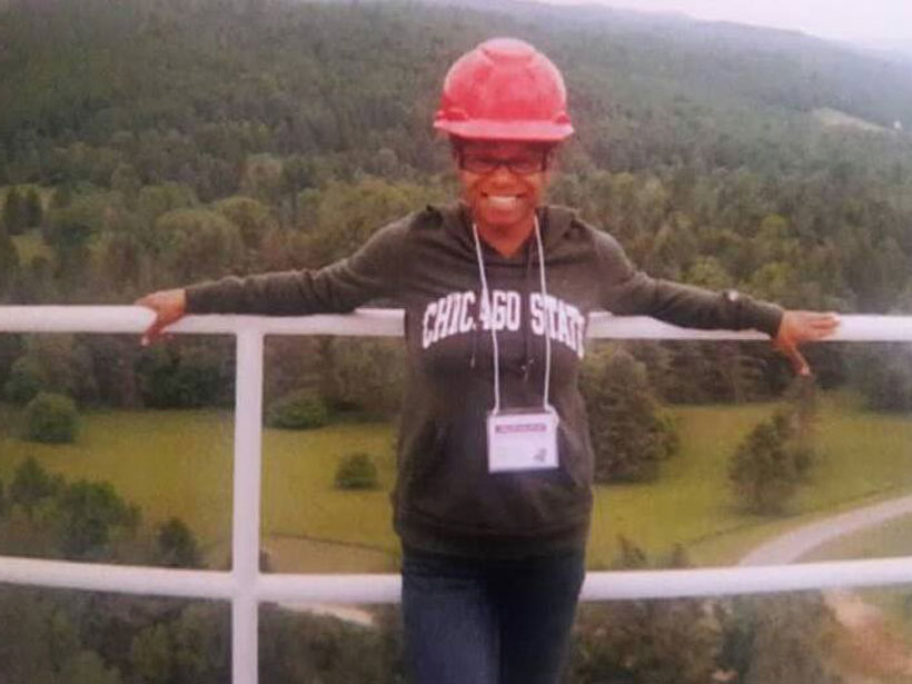 Ashley Walker stands against a railing on a platform overlooking the wooded mountains surrounding the Green Bank Telescope in West Virginia.