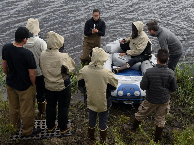 Peter demonstrates water sampling to environmental science students.
