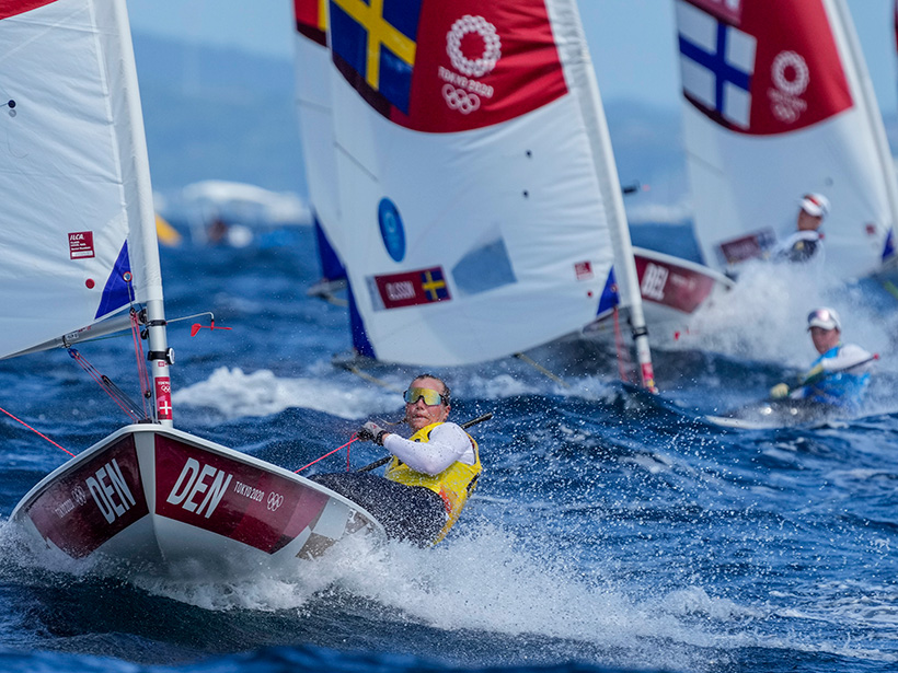 """A white woman wearing a long-sleeved white shirt, yellow vest, and tinted goggles leans over the side of a sailboat during an Olympic sailing competition. The boat, labeled """"DEN"""" and with a white and red sail, is positioned toward the left side of the image facing forward and is surrounded by sprays of water. In the background are four more sailboats with white and red sails, and country flags fly."""