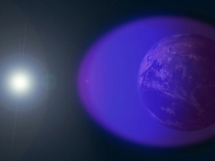 A layer of charged particles, known as the ionosphere, surrounds Earth, shown in purple (not to scale) in this image.