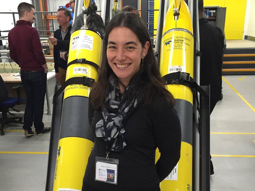 Scientist Jennifer Arrigo stands in front of ocean gliders.