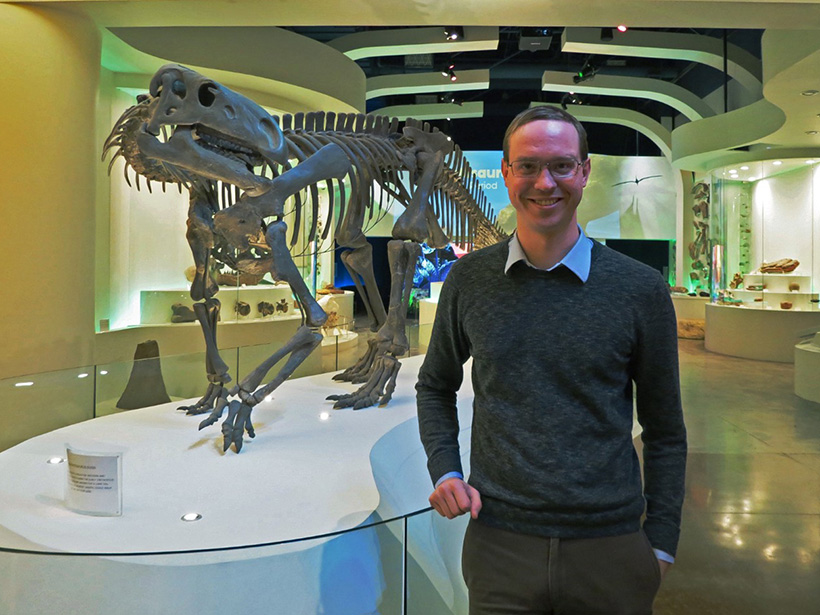 A smiling man about 30 years old stands in a brightly lit museum exhibit hall next to a meter-tall dinosaur fossil that stands on a platform.