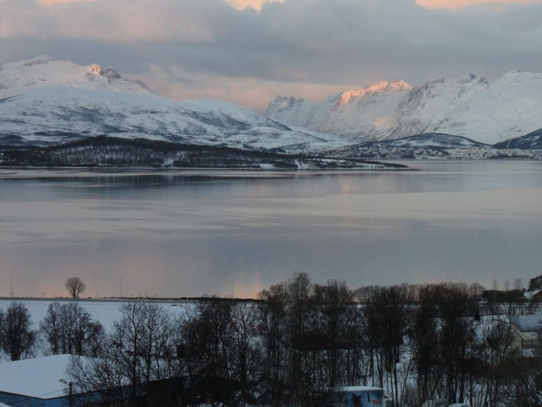 A coastal waterway in front of snow covered mountains