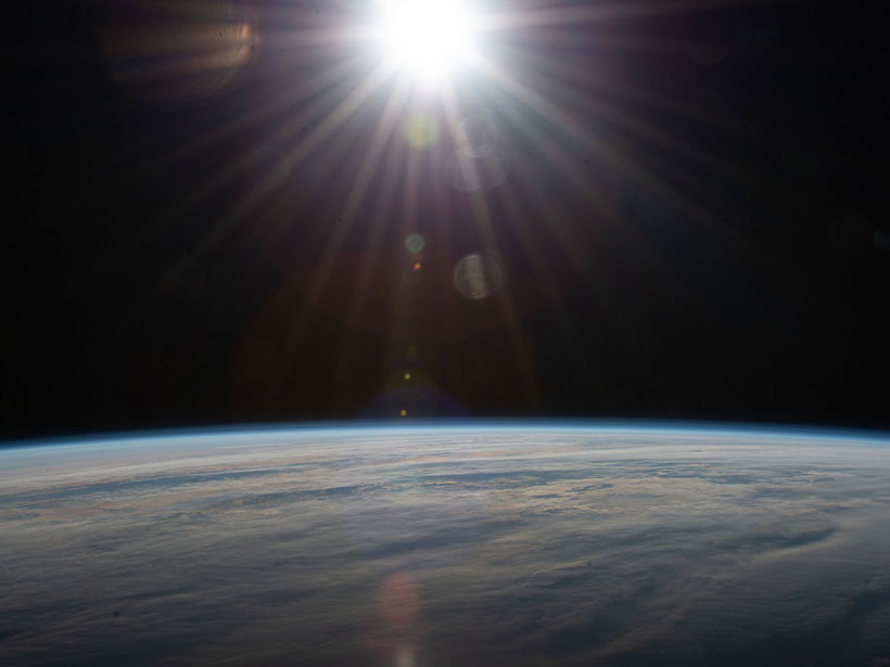 A burst of sunlight above a cloudy Earth.