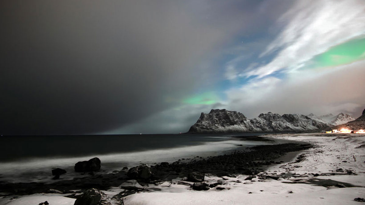 A dark cloud bank hovers over the water off of a rocky beach