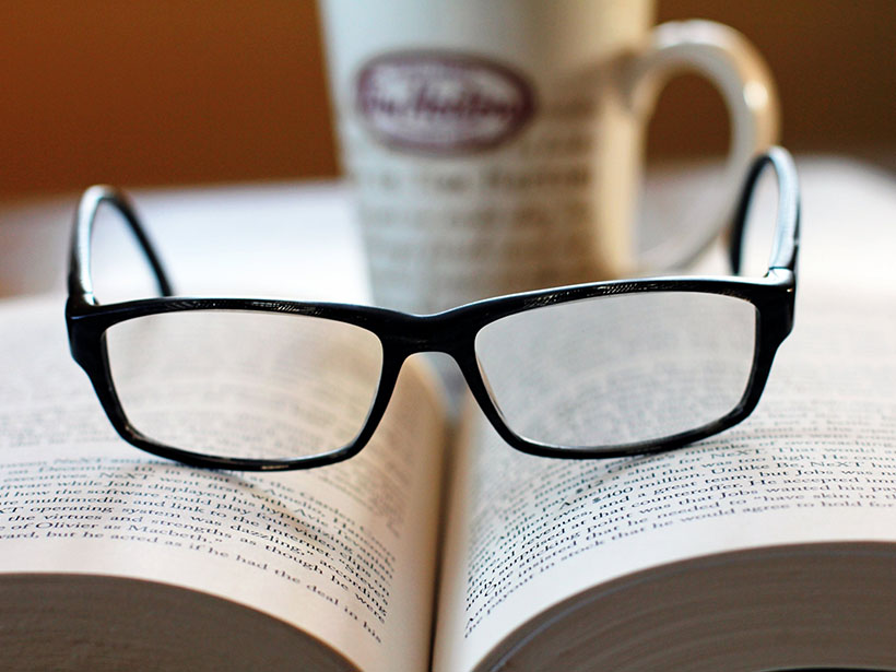 A photo of glasses on top of an open book
