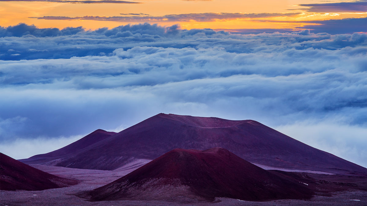 Orange sky from a sunrise fills the sky beyond a mountain summit and clouds.