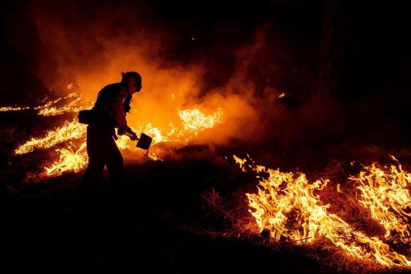 Bombeiro luta contra as chamas durante a noite na Floresta Nacional de Los Angeles.