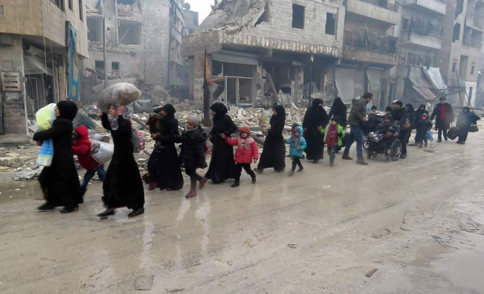 Civiles y niños sirios abandonan un barrio de Alepo de Bustan al-Qasr en dirección al de Fardos, el 13 de diciembre.