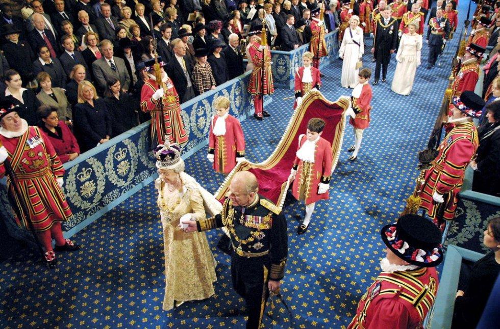 La reina Isabel II de Inglaterra acompañada por su esposo el Duque de Edimburgo, en procesión oficial por la Royal Gallery (Galería Real), camino de la Cámara de los Lores, en Londres (Reino Unido), donde presidió la apertura del año parlamentario, el 13 de noviembre de 2002.