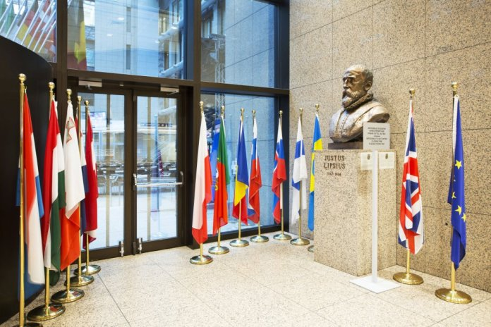 Una bandera del Reino Unido, también conocida como Union Jack, cuelga entre una bandera de la Unión Europea (UE) y un busto de Justus Lipsius, filólogo y humanista flamenco, dentro de un pasillo del edificio Justus Lipsius, la sede del Consejo Europeo.