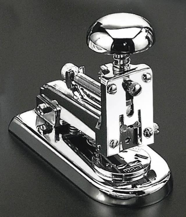 """Fíjate en esta grapadora, porque según el experto Juli Capella, es """"el Rolls Royce de las grapadoras, la mejor del mundo"""". La inventaron en 1935 dos industriales vascos, Olabe y Solozábal, que hasta entonces se habían dedicado a la producción de armamento. La empresa que se la encargó por aquel entonces, El Casco, sigue produciéndola hasta el día de hoy, con un diseño que apenas ha sufrido cambios: su sistema de muelles la hace cómoda y rápida, y la dureza de su material permite que siga en su sitio durante décadas. Se sabe de grapadoras que han sobrevivido a varias generaciones."""