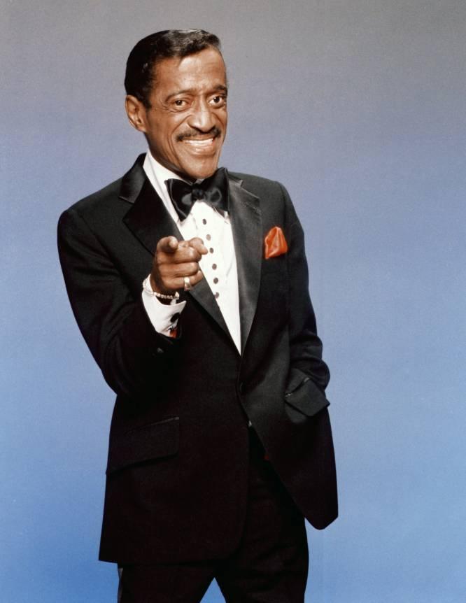 """""""Tenho a consciência tranquila"""", costumava dizer a seus amigos um Sammy Davis Jr. (Nova York, 1925- Califórnia, 1990) completamente arruinado. """"Não devo dinheiro a ninguém que precise, quase todas as minhas dívidas são com o governo dos Estados Unidos"""". Essas dívidas chegaram a somar quase 15 milhões de dólares, porque o cantor do Harlem, como muitos outros famosos, adquiriu o hábito de deixar de pagar impostos quando sentiu que eram um luxo que não podia se permitir. Nos melhores anos de sua carreira, entre fim dos anos 40 e meados dos 60, quando fazia parte do 'Rat Pack' de Frank Sinatra, Sammy ganhava mais de um milhão de dólares por ano com suas turnês. Em 1989, já na bancarrota devido a péssimos investimentos e luxos excêntricos, decidiu não extirpar um tumor na garganta porque temia que a operação afetasse suas cordas vocais. """"Não tenho um centavo guardado, e se não posso continuar cantando, vou morrer de fome"""", foi o que argumentou. Muito pouco depois acabou morrendo por conta do tumor que não quis operar. Na imagem, Sammy Davies Jr. em Los Angeles, em 1988."""