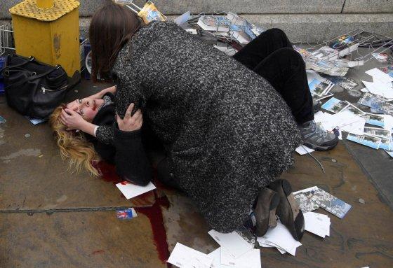 """Mulher ajuda uma das vítimas do atropelamento na ponte de Westminster, em Londres (Grã-Bretanha), em 22 de março de 2017. Foto indicada nas categorias """"Foto do Ano"""" e """"Temas atuais"""", feita pelo fotógrafo Toby Melvill, da agência Reuters."""