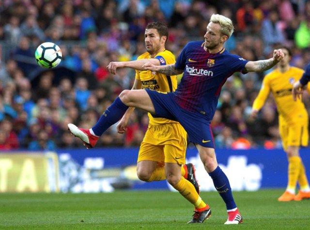 El mediocentro croata del FC Barcelona, Ivan Rakitic lucha por el balón frente al centrocampista del Atlético de Madrid, Gabi Fernández.