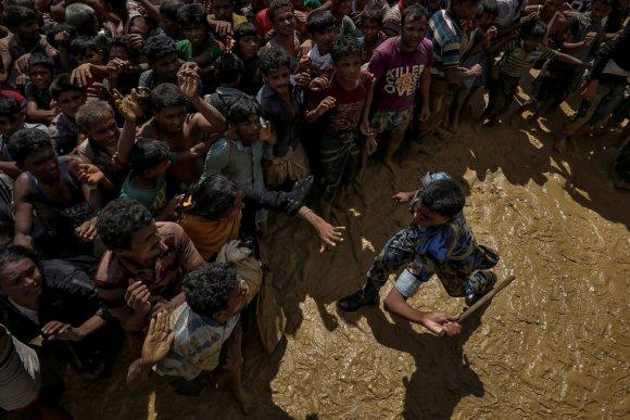 Um oficial de segurança tenta controlar os refugiados rohingyas que aguardam ajuda no Cox's Bazar (Bangladesh), em 21 de setembro de 2017.