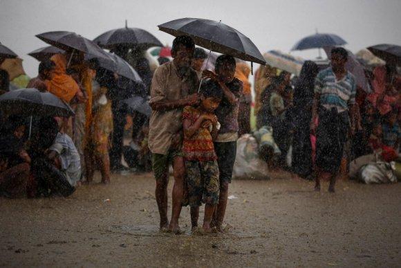 Refugiados rohingyas tentam se proteger das chuvas torrenciais enquanto estão retidos pela Guarda de Fronteiras de Bangladesh (BGB), depois de atravessar ilegalmente a fronteira, em Teknaf (Bangladesh), em 31 de agosto de 2017.