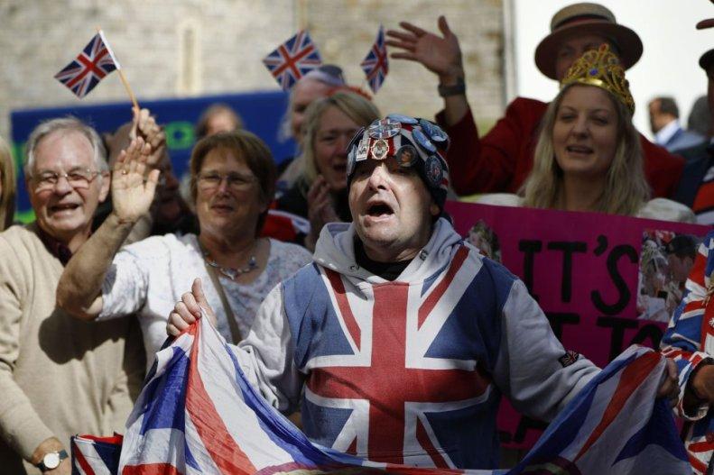 John Laughry (C) y otros seguidores de la familia real esperan en los alrededores del castillo de Windsor, donde se celebrará el enlace de Enrique y Meghan.