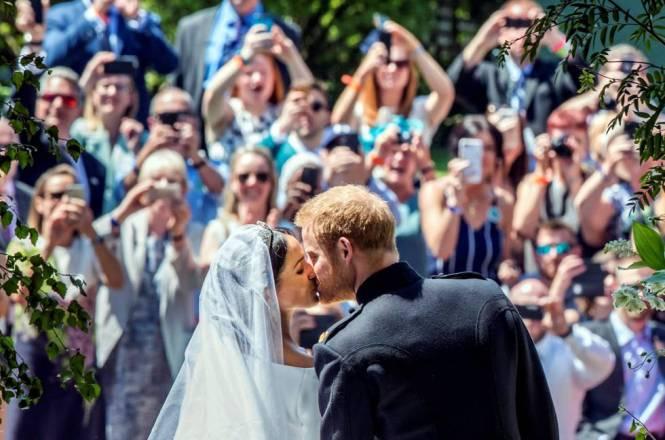 Los recién casados Enrique y Meghan se besana a la salida de la capilla.