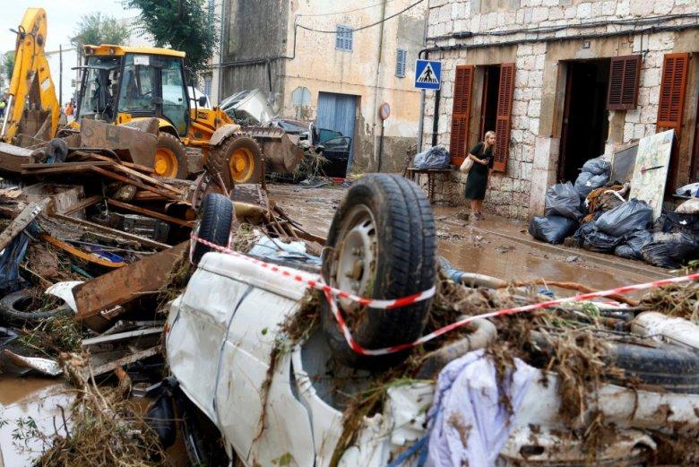 Una mujer intenta caminar entre los destrozos causados por las inundaciones y el desbordamiento de torrentes, en Sant Llorenç des Cardassar (Mallorca).