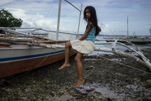 Una niña posa sentada en un banka, en una playa de Taytay.